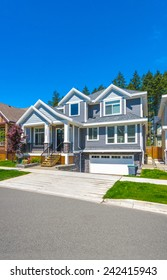 Custom built luxury house with nicely trimmed and landscaped front yard lawn and driveway to garage in a residential neighborhood. Vancouver Canada. Vertical.