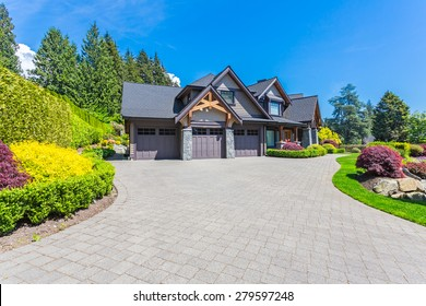 Custom built luxury house with nicely trimmed front yard, lawn in a residential neighborhood in North America on a sunny day.