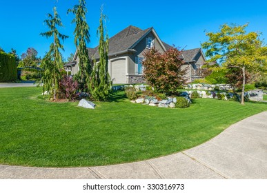 Custom built luxury house with nicely trimmed and designed front yard, lawn in a residential neighborhood. Vancouver Canada.
