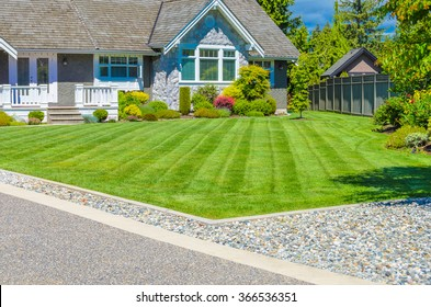 Custom built luxury house with nicely trimmed and landscaped front yard, lawn and driveway in a residential neighborhood. Vancouver Canada. Vertical.