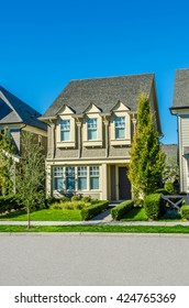 Custom built luxury house, townhouse with nicely trimmed and landscaped front yard, lawn in a residential neighborhood. Vancouver Canada.
