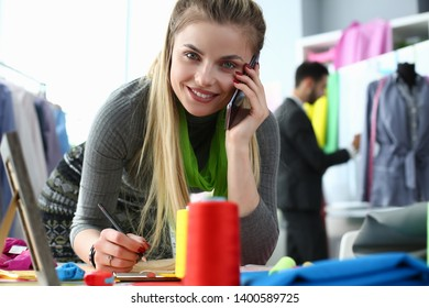 Custom Clothes Tailoring Service Designer on Phone. Smiling Woman Calling, Writing Notes. Caucasian Needlewoman Creating Draft at Sewer Working Table. Happy Beauty Looking at Camera
