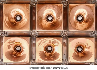 A custom copper light fixture creates an interesting pattern with six light bulbs reflecting from the metal.