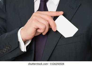 Custom debit card design. Male hand put plastic blank white card to pocket classic suit jacket. Business man carries credit card. Banking services for business. Custom design making your card unique.