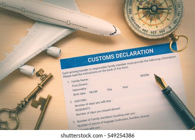 Custom declaration form on a wood table with a white model airplane. The purpose of the form is to declare what goods are been brought in to the nation, as some may have limits or customs excise tax.