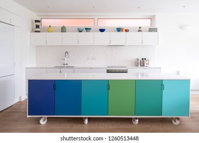 Custom designed kitchen island in painted MDF, in open plan kitchen on industrial castor wheels, retro design painted in blue and green ombre colours.