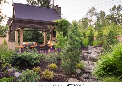 An custom designed shelter is seen beyond a perennial garden featuring a dry stream bed.