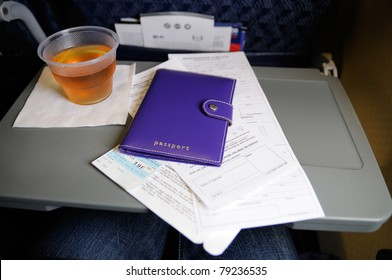 Custom forms and passport on the seat tray aboard an airline flight