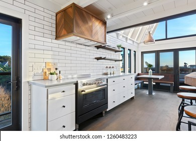 Custom Kitchen with Floor to Ceiling Windows, Copper Accents, and Subway Tile