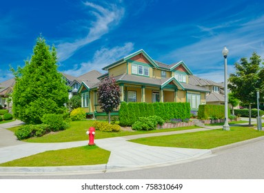 Custom made luxury house with nicely landscaped and trimmed front yard and driveway to garage in the suburbs of Vancouver, Canada.