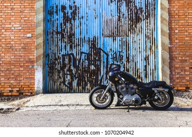 Custom motor bike holds on a vintage industrial street. Outdoor portrait and urban lifestyle
