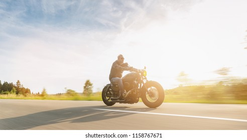 custom motorbike riding on the road. having fun driving the empty road on a motorcycle tour journey. copyspace for your individual text.