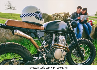 Custom motorcycle with helmet and young couple sitting looking at a map. Selective focus on motorcycle in foreground