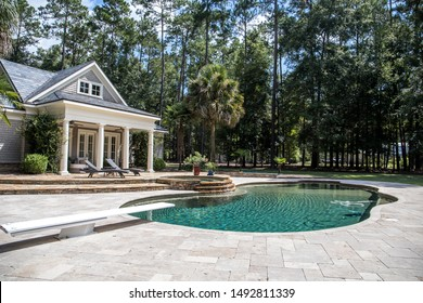 Custom pool House behind an estate with a large swimming pool