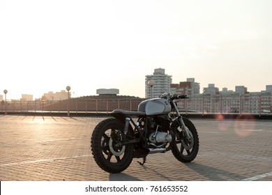 Custom vintage motorcycle cafe racer on empty rooftop parking lot during sunset. Hipster lifestyle, student dream
