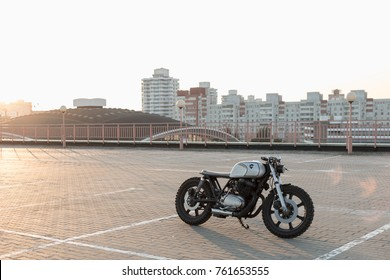 Custom vintage motorcycle cafe racer on empty rooftop parking lot during sunset. Side view. Hipster lifestyle, student dream