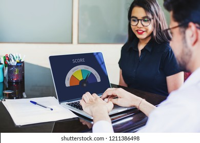 Customer assessment in bank. Credit score on a screen of laptop appears as Indian credit scoring officer evaluates the female client.