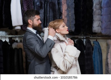 Customer with beard and woman buy furry coat. Finance and shopping concept. Man with wallet and girl on clothes rack background. Couple in love tries expensive pink mink overcoat on