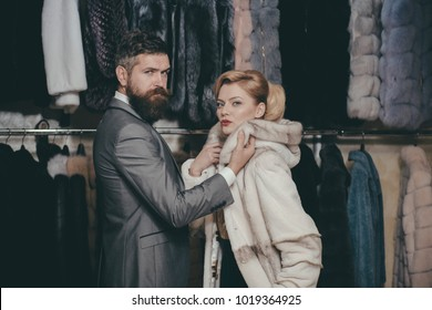 Customer with beard and woman buy furry coat. Finance and shopping concept. Couple in love tries expensive overcoats. Man and girl with busy faces count money in blue wallet on clothes rack background
