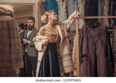 Customer with beard and woman buy furry coat. Finance and shopping concept. Man with wallet and girl with happy faces on clothes rack background. Couple in love tries expensive mink overcoat on