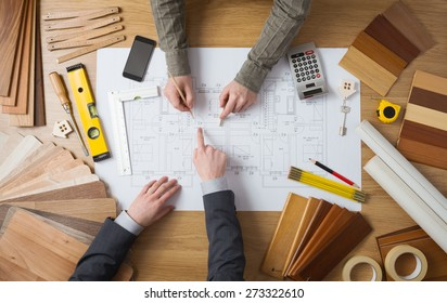 Customer businessman and construction engineer working together on a building project, desktop top view