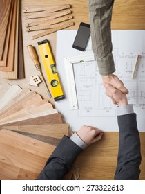 Customer businessman and construction engineer working together on a building project, they are shaking hands, desktop with draft and tools on background, top view