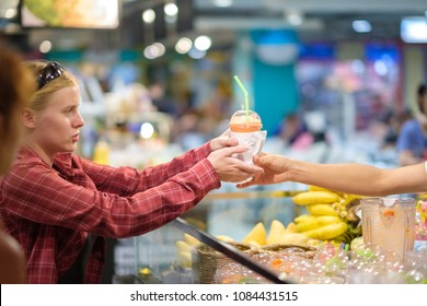 Customer buy fruit drink on food court holding plastic cup with straw