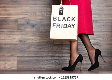 Customer buyer legs of woman female adult with shopping bag with sale label and black high heels walking to fashion shopping mall store in black friday holiday to discover sale and discount price.