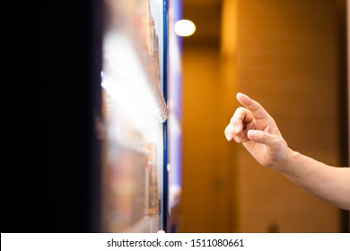 A customer buying beverage at a vending machine