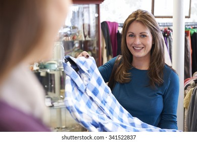Customer Buying Clothing In Charity Shop