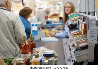 Customer buying food at supermarket and making check out with cashdesk worker in store. Shopping, sale, consumerism and people concept. 7 September 2018. Amsterdam. Netherlands