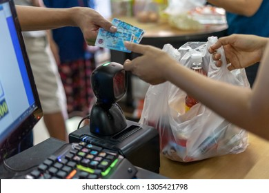 Customer buying things at Pracharat shops or Grocery shop carrying blue flags approved by the Commerce Ministry of Thailand. The cards can only be used at shops have EDC readers.