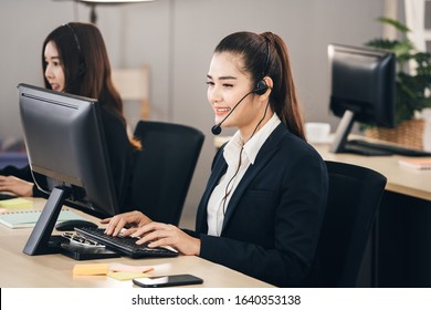 Customer call center service care concept. Positive smile young business staff asian woman using headphone and computer for support and organize as a teamwork in office.