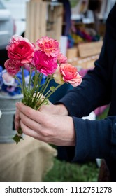 A customer chooses a bright bunch of Ranunculus flowers at a Farmers' Market