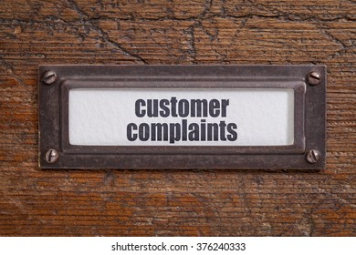 customer complaints  tag - file cabinet label, bronze holder against grunge and scratched wood