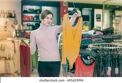 Customer deciding on pretty blouse in womens cloths shop