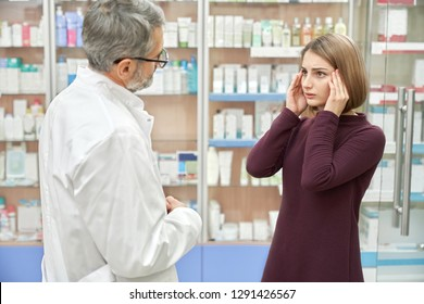 Customer of drugstore talking and consulting with pharmacist. Woman grabbing head. Chemist helping, offering medicaments from headache. Mature man wearing in white coat and glasses.