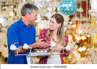 Customer in electrical good department of hardware store asking clerk for help concerning lighting