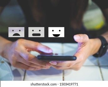 Customer experience concept, happy business women holding the smartphone with a checked box on excellent smiley face and rating for a satisfaction survey.