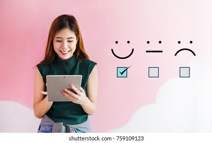 Customer Experience Concept, Happy Client Woman holding digital Tablet with a checked box on Excellent Smiley Face Rating for a Satisfaction Survey
