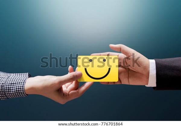 Concepto de experiencia del cliente, mujer cliente feliz dando un voto con tarjeta de cara sonriente feliz en una mano de hombre de negocios
