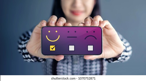 Customer Experience Concept. Happy Woman Show her Satisfaction on Smart Phone with a checked box on Excellent Smiley Face Rating