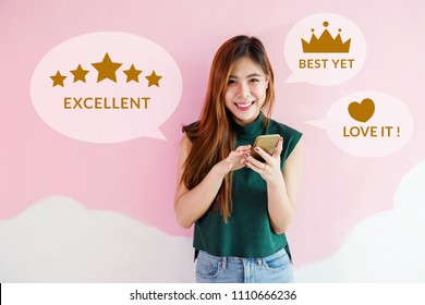 Customer Experience Concept. Happy Young Woman using Smart Phone to Review and Feedback Rating in Online Satisfaction Survey Application. Looking at camera with Smile