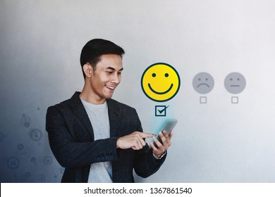 Customer Experience Concept. Young Businessman Giving his Positive Review in Satisfaction Online Survey. Happy Client Submit a Smiling Face for Excellent Services via Smartphone