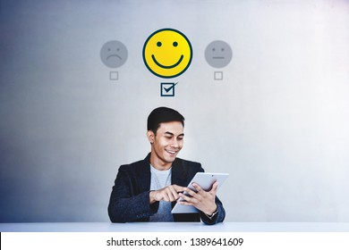 Customer Experience Concept. Young Businessman Giving his Positive Review in Satisfaction Online Survey. Happy Client Submit a Smiling Face for Excellent Services via Tablet