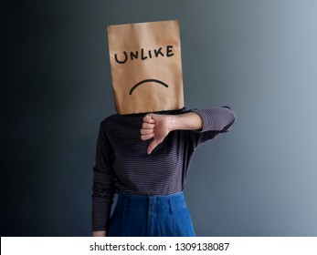 Customer Experience or Human Emotional Concept. Woman Covered her Face by Paper Bag. present Disappointed Feeling by Thumb Down Gesture Sign and Unlike Text