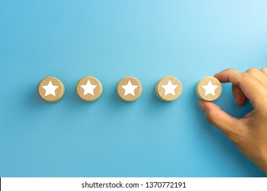 Customer experience, satisfaction survey, Evaluation, Increase rating and best excellent services rating concepts. The client's hand picked the five star symbol on wooden cubes on blue background.