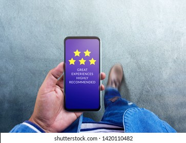Customer Experiences Concept. Five Stars Rating and Positive Review show on Smartphone's Screen. a Modern Man Reading Client's Satisfaction Surveys via Mobile Phone. Top View
