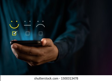 Customer Experiences Concept. Modern Man Giving a Smiling Emoticon Rating, Positive Review via Smartphone. Client's Satisfaction Surveys on Mobile Phone. Front View