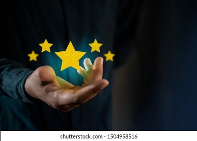 Customer Experiences Concept. Person Giving Positive Review for Client's Satisfaction Surveys. Five Stars Rating floating on Hand. Dark Tone